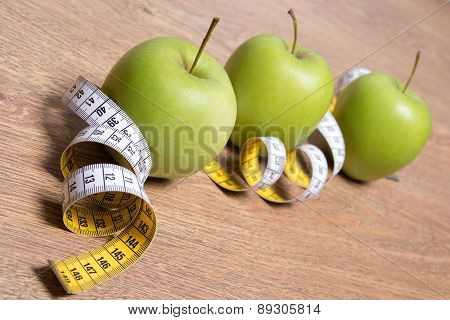 Diet Concept - Close Up Of Green Apples And Measure Tape On Table