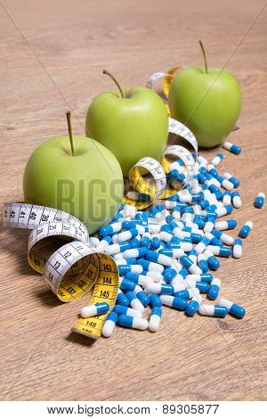 Diet Concept - Green Apples, Pills And Measure Tape On Table