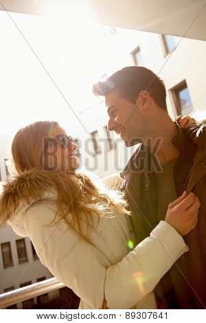 Happy loving couple embracing at wintertime in sunlight.
