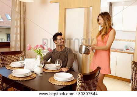 Young couple waiting for friends at home to have dinner together. Woman serving soup.