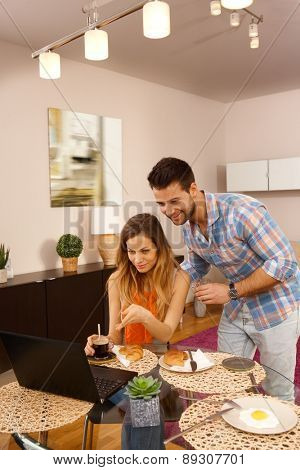 Young couple having breakfast and using internet at home, having laptop computer.
