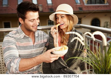 Romantic couple sitting on balcony, eating, smiling, hugging.