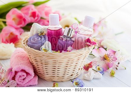 Spa bath toiletries set in basket with fresh flowers