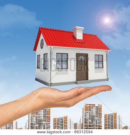House under businesswomans hand with cityscape