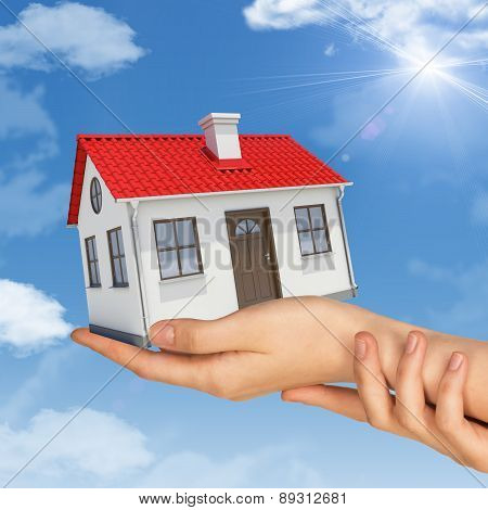 Womans hands holding house