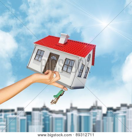 House and keys in womans hand with cityscape