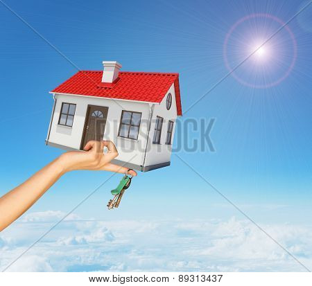 House and keys in womans right hand under clouds