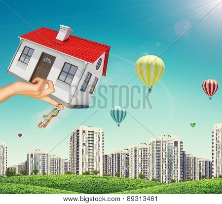 House and keys in businesswomans hand on cityscape