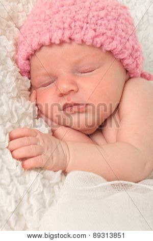 Newborn baby girl wearing a pink knitted hat.