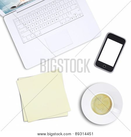 White laptop with note paper and mobile, top view