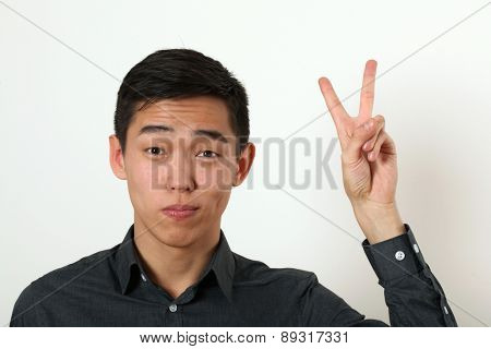 Pleased young Asian man giving the victory sign and looking at camera.
