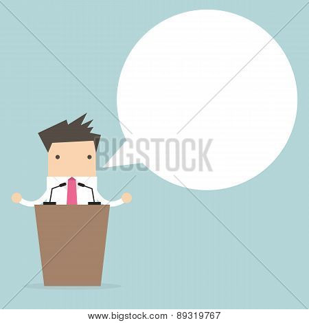 Businessman standing on podium and giving a speech