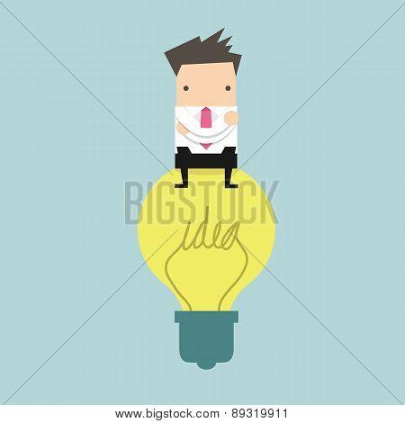 Businessman sitting on idea bulb