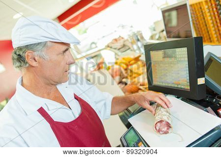 Butcher weighing cured meat