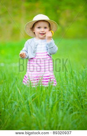 little daughter standing with hat on in green summer grass