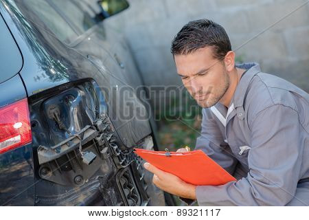 Mechanic taking notes as he assesses a car