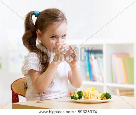 Cute little girl drinking water