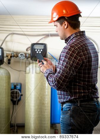 Engineer Taking Meter Readings From Industrial Pumps At Factory