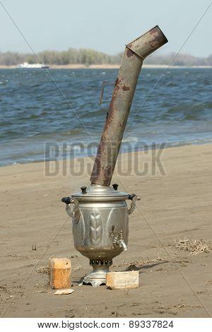 samovar on the sand near river