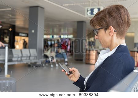 Waiting In Airport Terminal Using Phone