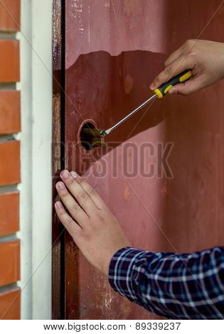 Closeup Of Carpenter Trying To Open Door Lock Using Screwdriver