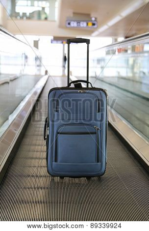 Blue suitcase on conveyor belt.