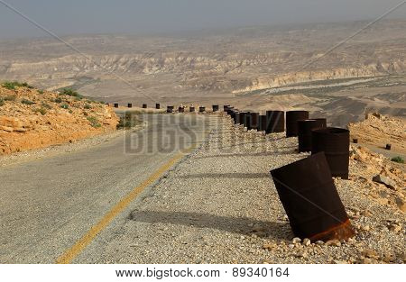 Mountain desert road with barrels winding left.