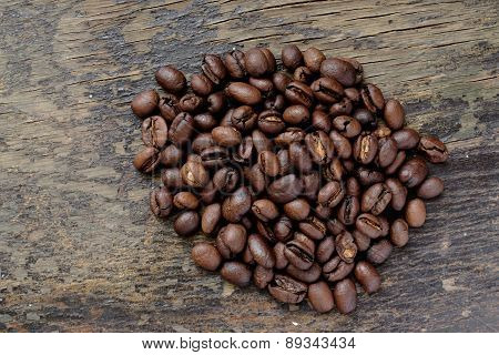 Coffee Beans In Coffee Bag Made From Burlap On Wooden Surface With Dramatic Light.