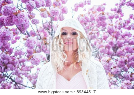 Gorgeous dreamy young woman with long blond hair standing in spring blossom looking up into the air with a faraway expression, close up view of her face