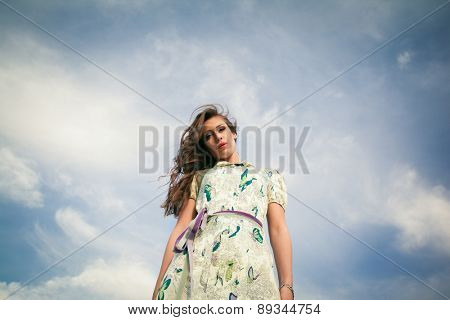 young woman in summer  dress against sky look at camera from above