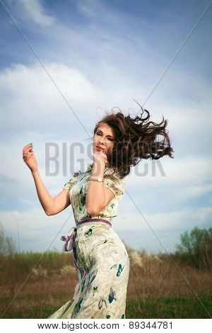 young woman in summer  dress in motion on grass field