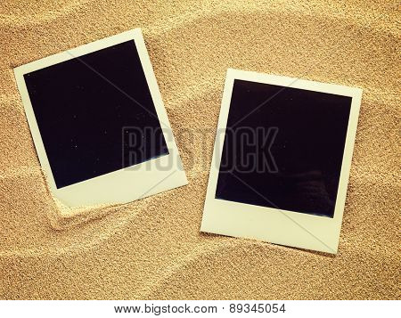 Empty photo cards in retro style  lying on a sea sand. Sunny summer background. Space for your text.