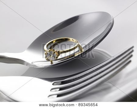 Diamond Ring in silver spoon isolated on white background