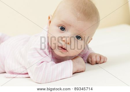 portrait of lying three months old baby girl