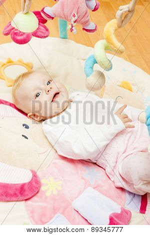 portrait of baby girl lying on playing mat
