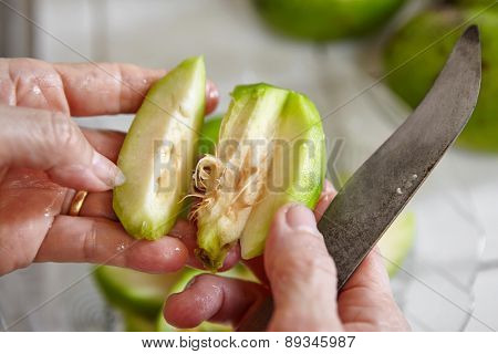 Peeling and cutting ambarella fruit or known as kedondong in Indonesia
