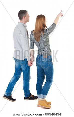 Back view of walking young couple (man and woman) pointing. Rear view people collection. backside view of person. Isolated over white background. girl holding hand of Man, and shows his hand forward.