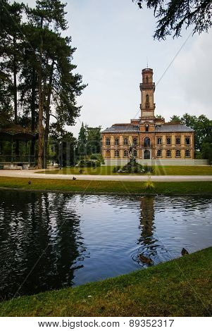 House With  Turret And Its Reflection In The Lake