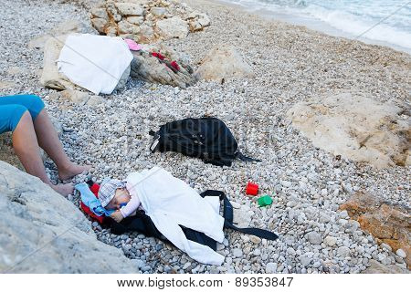 Sleeping Baby Lying On A Pebbled Beach
