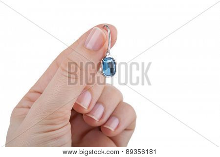 Female hand holding a sapphire earring