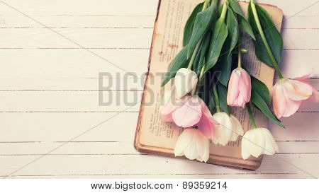 Background With Fresh  Tulip Flowers On Old Book