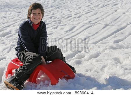 Young Boy Having Fun On The Red Sleigh In The Mountains In Winter