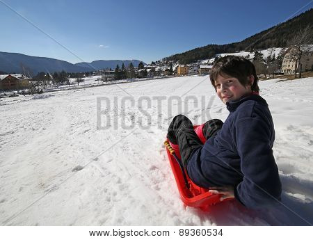 Young Boy Having Fun On The Red Sleigh In The Mountains