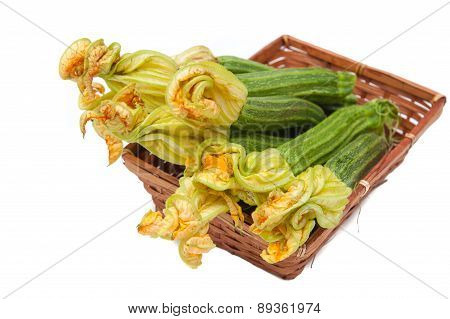 Courgettes  With Flowers In Brown Basket Focus On Flowers Isolated
