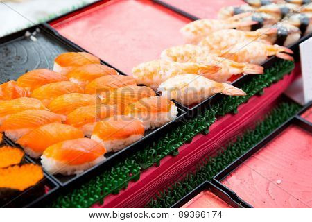 cooking, asian kitchen, sale and food concept - sushi sets at street market