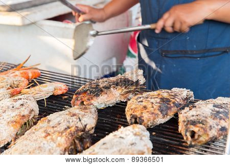 cooking, asian kitchen, sale and food concept - close up of cook hands grilling fish at street market