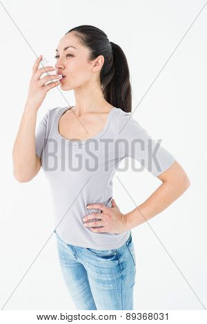 Asthmatic pretty brunette using inhaler on white background