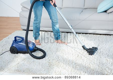 Woman using vacuum cleaner on carpet at home in the living room