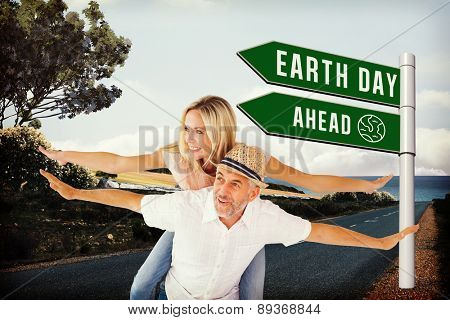 Happy man giving his partner a piggy back against scenic backdrop