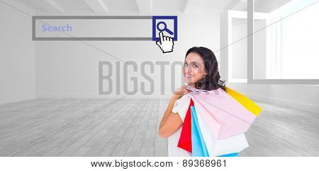 Pretty brunette with shopping bags against white room with opened windows